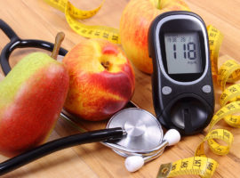 a glucose monitor, a stethoscope and some fruit on a table