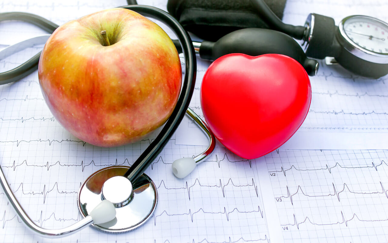 a heart shaped toy, a blood pressure monitor, a stethoscope and an apple on top of a cardiogram