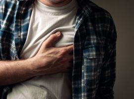 man with unbuttoned shirt and white t-shirt holding his heart