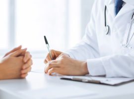 doctor writing on paper in front of a patient