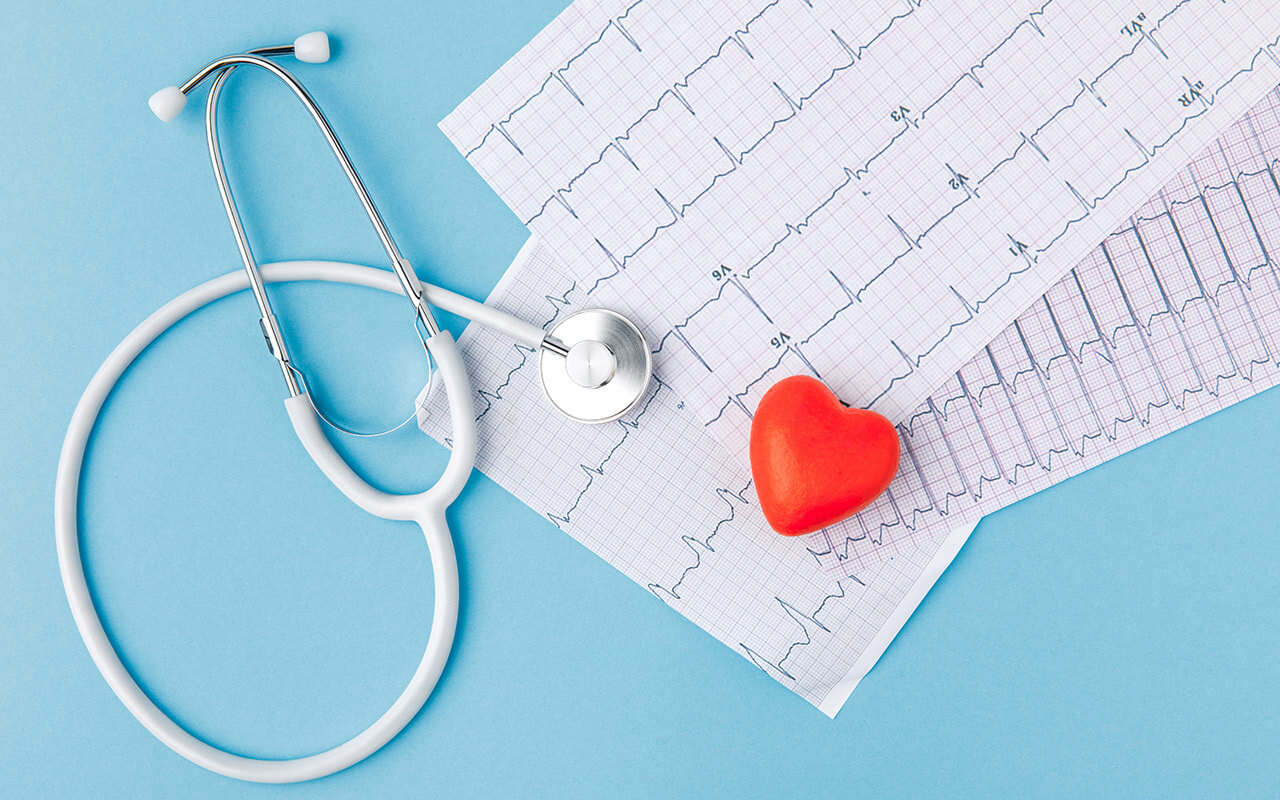 a heart shaped toy, a stesthoscope and a cardiogram on a blue table