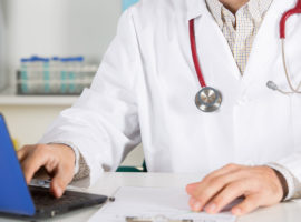 man with lab coat and stethoscope working on a laptop