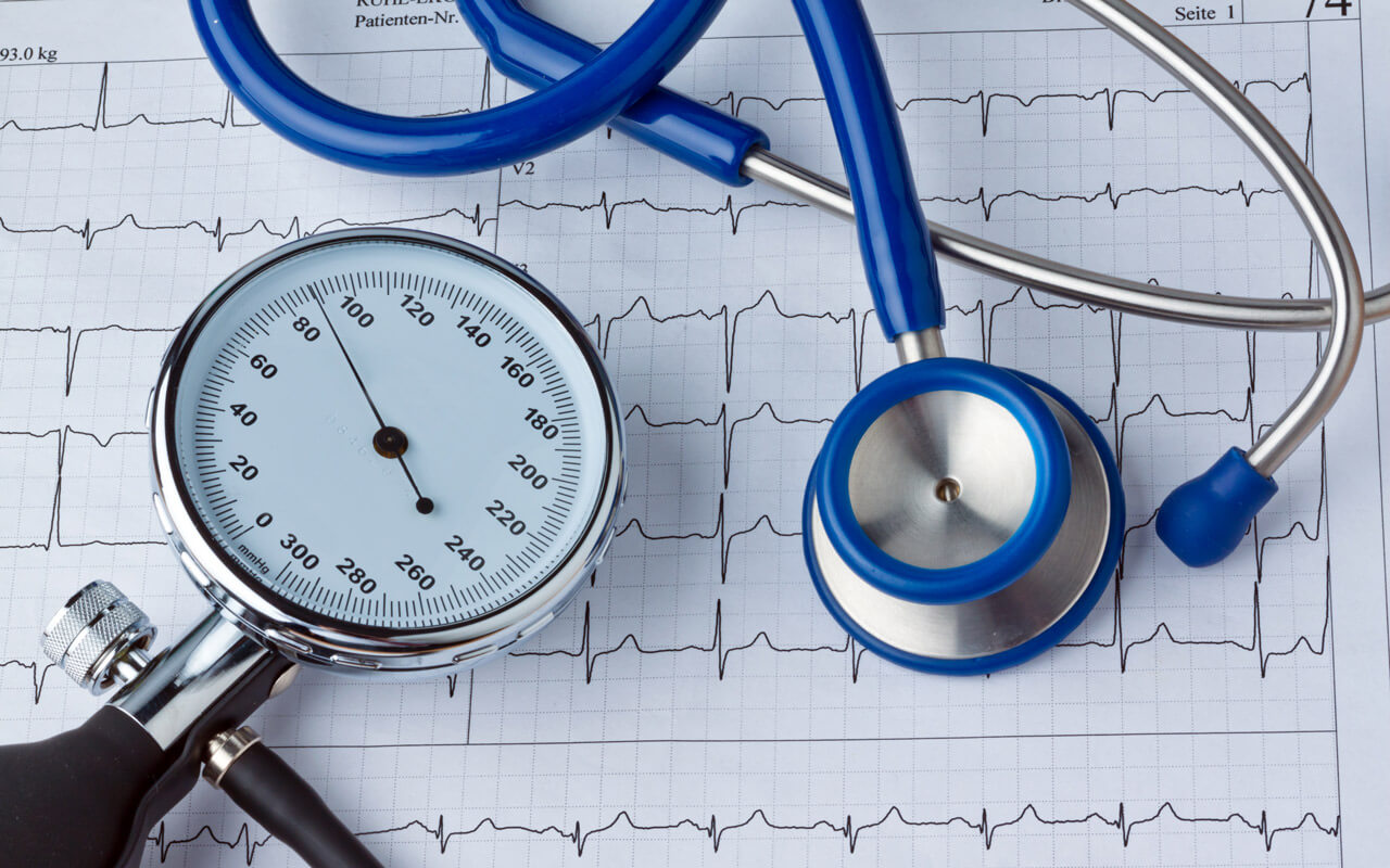 a blood pressure monitor and a stethoscope on top of a cardiogram
